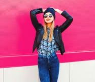 stilvolle glückliche lächelnde Frau des Porträts in der Felsenschwarz-Artjacke, Hut, der auf Stadtstraße über bunter rosa Wand au stockfotografie