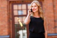 Stilvolle glückliche blonde Frau, die auf Telefon und dem Lächeln spricht Stockfotografie