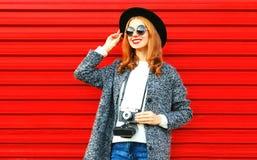 Stilvolle hübsche Frau mit Retro- Kamera auf einem Rot Lizenzfreies Stockbild