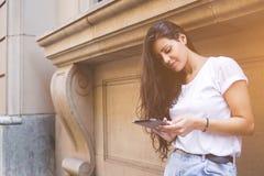 Stilvolle Hippie-Frau grast Internet für Navigation in der städtischen Landschaft während der Erholung Lizenzfreie Stockbilder