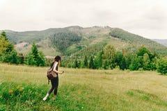 Stilvolle Hippie-Frau mit dem Rucksack, der Wildflowers in mou erfasst Stockbilder