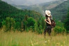 Stilvolle Hippie-Frau mit Rucksack, das erstaunliche Holz betrachtend Stockfotos
