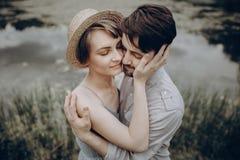Stilvolle Hippie-Paare, die am See umarmen Mann und Frau in modernem lizenzfreies stockbild