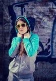 Stilvolle Jugendliche in der bunten Sonnenbrille, die nahe Graffiti aufwirft Lizenzfreies Stockfoto