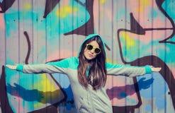 Stilvolle Jugendliche in der bunten Sonnenbrille, die nahe Graffiti aufwirft Stockbild