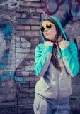 Stilvolle Jugendliche in der bunten Sonnenbrille, die nahe Graffiti aufwirft Lizenzfreie Stockfotografie