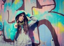 Stilvolle Jugendliche in der bunten Sonnenbrille, die nahe Graffiti aufwirft Stockfoto