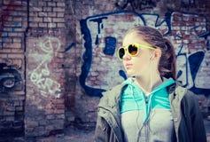 Stilvolle Jugendliche in der bunten Sonnenbrille, die nahe Graffiti aufwirft Lizenzfreies Stockbild