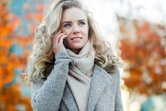 Stilvolle junge blonde Frau, die draußen am Telefon spricht Lizenzfreies Stockbild
