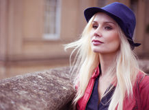 Stilvolle junge blonde Frau, die draußen wartet Lizenzfreies Stockbild