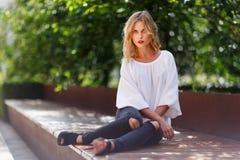 Stilvolle junge blonde Hippie-Frau, die auf Parkbank stillsteht Lizenzfreies Stockfoto