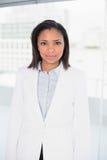 Stilvolle junge dunkelhaarige Geschäftsfrau, die Kamera betrachtend aufwirft Stockfotografie