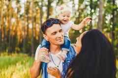 Stilvolle junge Familienmutter, -vati und -tochter ein jähriges blondes Sitzen mit Vater auf dem Schulterspielen glücklich und de stockbilder