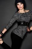 Stilvolle junge Frau über dunklem Hintergrund Stockfoto