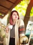 Stilvolle junge Frau auf Terrasse des Sommerrestaurants mit Tasse Kaffee lizenzfreie stockfotografie