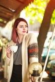 Stilvolle junge Frau auf Terrasse des Sommerrestaurants mit Tasse Kaffee stockfotografie