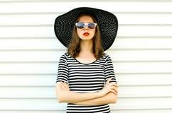 Stilvolle junge Frau des Porträts im schwarzen Sommerstrohhut, der auf weißer Wand aufwirft stockbild