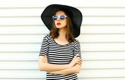 Stilvolle junge Frau des Porträts im schwarzen Sommerstrohhut, der auf weißer Wand aufwirft stockfotografie