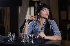 Stilvolle junge Frau, die allein an der Bar trinkt Stockfotos