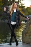 Stilvolle junge Frau, die gegen See im Park aufwirft Stockbilder