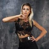 Stilvolle junge Frau im schwarzen Spitzenoberteil und im Rock Stockfotografie