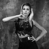 Stilvolle junge Frau im schwarzen Spitzenoberteil und im Rock Stockfoto