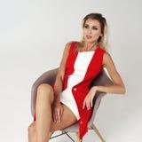 Stilvolle junge Frau im weißen Kleid und in der roten Jacke Lizenzfreies Stockfoto