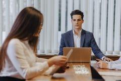 Stilvolle junge Leute in der modernen Büroarbeit bei einem Schreibtisch mit Dokumenten und einem Laptop stockfotografie