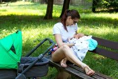 Stilvolle junge Mutter, die Elternteil das schöne Baby pflegt, das durch grünes Gras im Allgemeinen Park, Dame umgeben wird, ist  Lizenzfreie Stockfotos