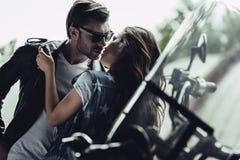 Stilvolle junge Paare, die draußen auf Motorrad umarmen und küssen stockbilder