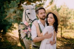 Stilvolle Jungvermählten, die nahe Pferd, Landhausstil umarmen lizenzfreie stockfotografie