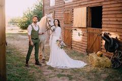 Stilvolle Jungvermählten stehen nahe Pferd und Blick in Kamera lizenzfreie stockbilder