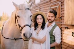 Stilvolle Jungvermählten stehen nahe Pferd und Blick in Kamera stockbild
