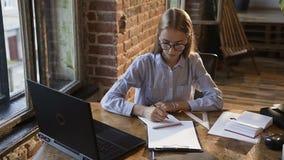 Stilvolle kaukasische junge Geschäftsfrau, die einen Laptop sitzt an einem Tisch im modischen Innenraum des Büroroten backsteins  stock footage