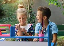 Stilvolle Kinder, Junge und Mädchen, die Schule spielt Im Freienfoto Bildung und Kindermodekonzept Stockbilder