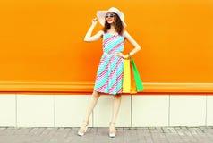 Stilvolle lächelnde Frau mit den Einkaufstaschen, die buntes gestreiftes Kleid, Sommerstrohhut aufwirft auf orange Wand tragen lizenzfreie stockfotos
