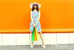 Stilvolle lächelnde Frau mit den Einkaufstaschen, die buntes gestreiftes Kleid, Sommerstrohhut aufwirft auf orange Wand tragen stockfotografie