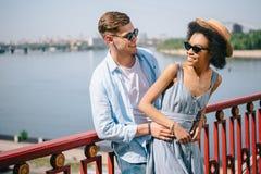 stilvolle lächelnde multiethnische Paare in der Sonnenbrille, die vorbei auf Brücke steht lizenzfreie stockfotos