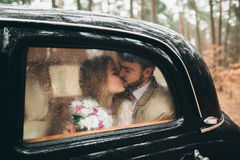 Stilvolle liebevolle Hochzeitspaare, die in einem Kiefernwald nahe Retro- Auto küssen und umarmen Stockfotos