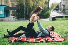 Stilvolle, liebevolle Paare, die am Park genießen Stockbild