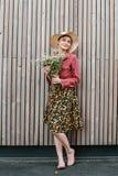 Stilvolle Mädchenstellung mit Blumen Schönheit nahe einer hölzernen Wand Fr?hlingsart Dieses Bild hat Freigabe befestigt Romantis stockbilder
