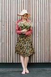 Stilvolle Mädchenstellung mit Blumen Schönheit nahe einer hölzernen Wand Fr?hlingsart Dieses Bild hat Freigabe befestigt Romantis stockfotografie