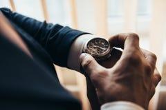 Stilvolle mechanische Uhr auf der Hand eines Mannes, der Zeit aufpasst lizenzfreie stockbilder