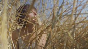 Stilvolle Modefrau mit der rauchenden Zigarette des kurzen Haares, die unter dem Weizenfeld weg schaut sitzt Überzeugtes sorglose stock footage