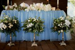 Stilvolle, moderne Hochzeitsbogenzeremonie verziert mit den Blauen und des Weiß verschiedenen Blumen Blumenauslegung? Hintergrund Stockfotografie