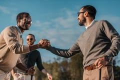 Stilvolle multikulturelle Freunde, die Hände beim Spielen des Golfs auf Golfplatz rütteln lizenzfreies stockbild