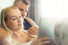 Stilvolle Paare, die auf das Sofa unter Verwendung der digitalen Tablette an ihrem modernen Haus streicheln Frau, welche die Tabl Lizenzfreies Stockfoto