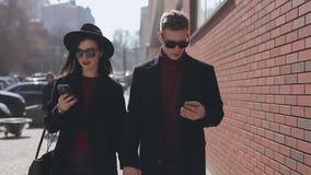 Stilvolle Paare, die unten ihre Smartphones gehen entlang Stadtstra?e untersuchen stock video footage