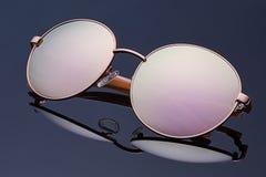 Stilvolle polarisierte reflektierte Sonnenbrille auf dunkelblauem Hintergrund Stockbilder