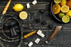 Stilvolle rauchende Huka und Korb mit Zitrone, Kalk und Orange an stockfotografie